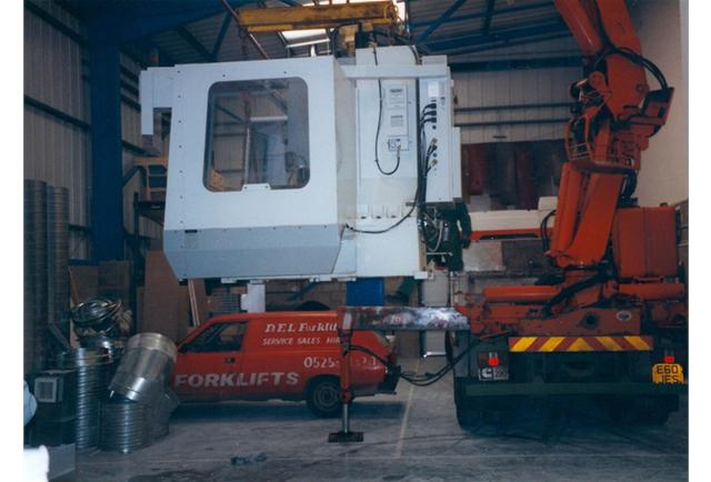 CNC machining centres being moved and installed.
